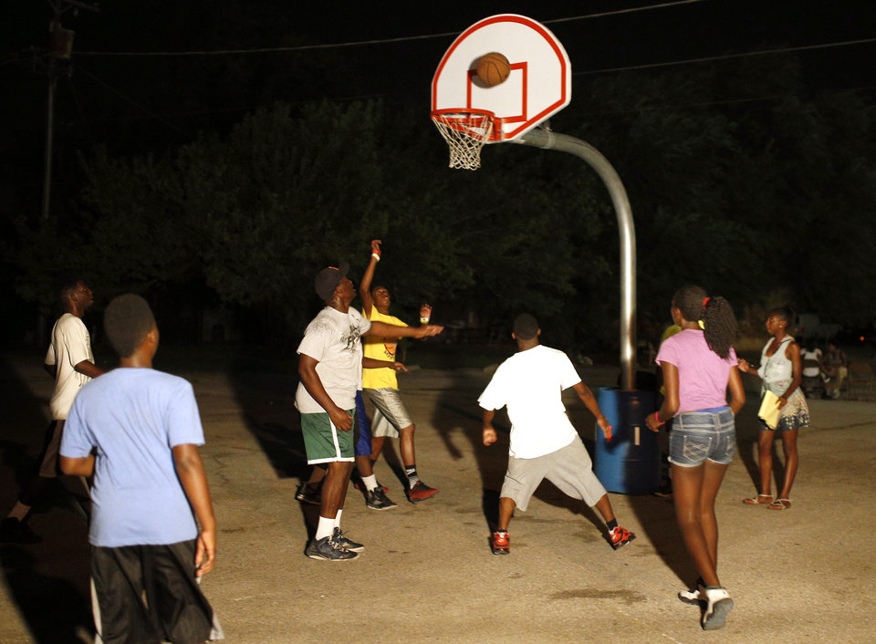 Photo - Youth play basketball during midnight basketball at Christ Temple Community Church in Oklahoma City, Friday, July 25, 2014. Photo by Sarah Phipps, The Oklahoman