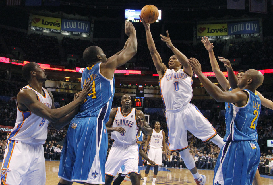 Photo - Oklahoma City Thunder point guard Russell Westbrook (0) drives to the basket past New Orleans Hornets power forward Carl Landry (24) and Jarrett Jack (2) during the NBA basketball game between the Oklahoma City Thunder and the New Orleans Hornets at the Chesapeake Energy Arena on Wednesday, Jan. 25, 2012, in Oklahoma City, Okla. Photo by Chris Landsberger, The Oklahoman