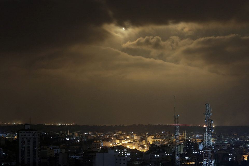 Photo - In this slow exposure photo, flares light the sky over Gaza as a trace of Israeli shelling, bottom right, is seen from Gaza City, in the northern Gaza Strip, Monday, July 28, 2014. A truce between Israel and Hamas militants in Gaza remained elusive as diplomats sought to end the fighting at the start of the Eid al-Fitr holiday, marking the end of the Muslim holy month of Ramadan. (AP Photo/Lefteris Pitarakis)