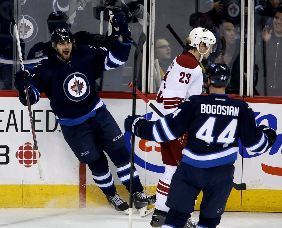 Photo - Winnipeg Jets' Eric O'Dell (58) celebrates after scoring with Zach Bogosian (44) as Phoenix Coyotes' Oliver Ekman-Larsson (23) looks on during first period NHL hockey action in Winnipeg, Canada, Monday, Jan. 13, 2014. (AP Photo/The Canadian Press, Trevor Hagan)