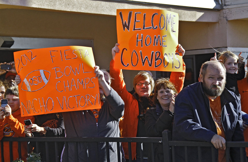 Oklahoma State fans cheer on their team as the Oklahoma State University football team arrives at the Stillwater Airport from their BCS Fiesta Bowl win on Tuesday, Jan. 3, 2012, in Stillwater, Okla. The Cowboys defeated Stanford 41-38 in overtime. Photo by Chris Landsberger, The Oklahoman