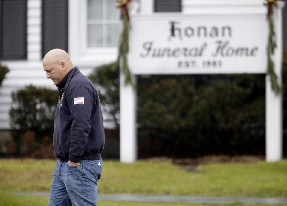 Photo - A mourner leaves a funeral service for Sandy Hook Elementary School shooting victim, Jack Pinto, 6, Monday, Dec. 17, 2012, in Newtown, Conn. Pinto as killed when a gunman walked into Sandy Hook Elementary School in Newtown Friday and opened fire, killing 26 people, including 20 children.(AP Photo/David Goldman) ORG XMIT: CTDG102
