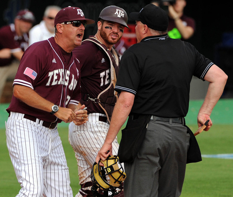 Photo - Texas A&M coach Rob Childress, left, argues with home plate umpire Frank Sylvester as catcher Troy Stein looks on after Sylvester ruled Texas' Tres Barrera safe at home during the eighth inning of an NCAA college baseball tournament regional game Friday, May 30, 2014, at Reckling Park in Houston. (AP Photo/Houston Chronicle, Eric Christian Smith) MANDATORY CREDIT