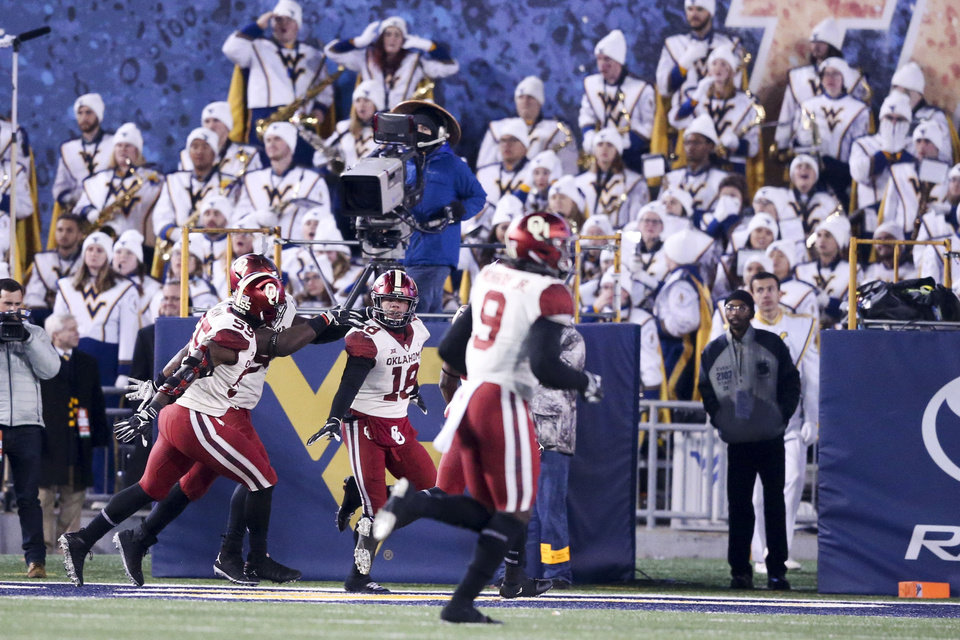 Photo - Oklahoma Sooners linebacker Curtis Bolton (18) celebrates with teammates after returning a fumble for a touchdown during the NCAA football game between the Oklahoma Sooners and the West Virginia Mountaineers at Mountaineer Field at Milan Puskar Stadium in Morgantown, W.Va on Friday, November 23, 2018. IAN MAULE/Tulsa World