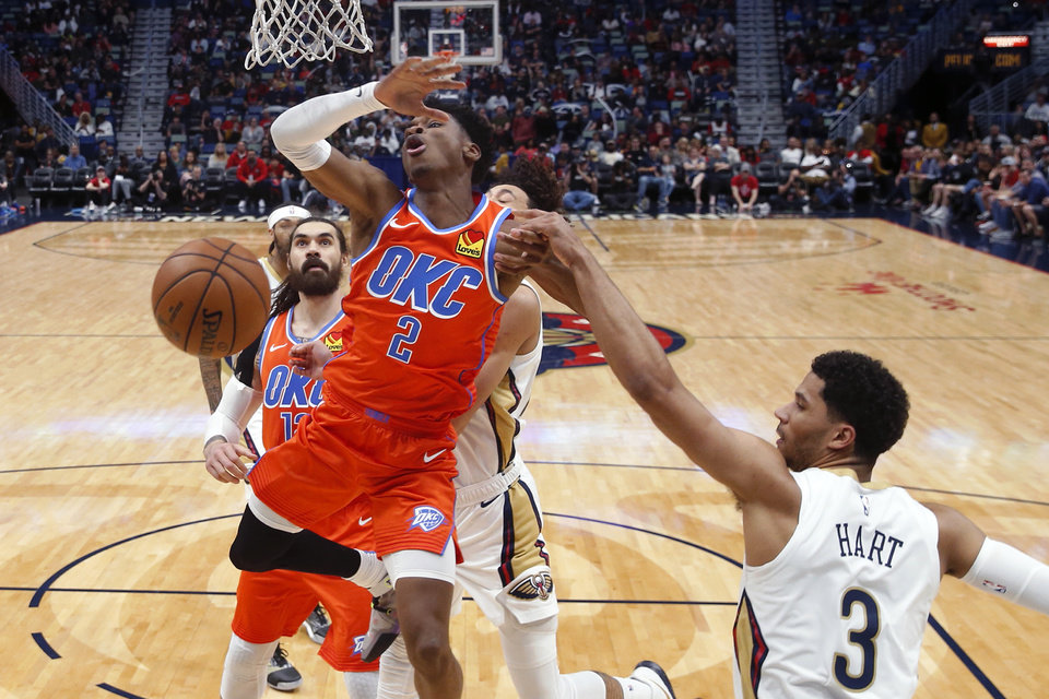 Photo - Oklahoma City Thunder guard Shai Gilgeous-Alexander (2) battles under the basket with New Orleans Pelicans guard Josh Hart (3) in the second half of an NBA basketball game in New Orleans, Sunday, Dec. 1, 2019. (AP Photo/Gerald Herbert)