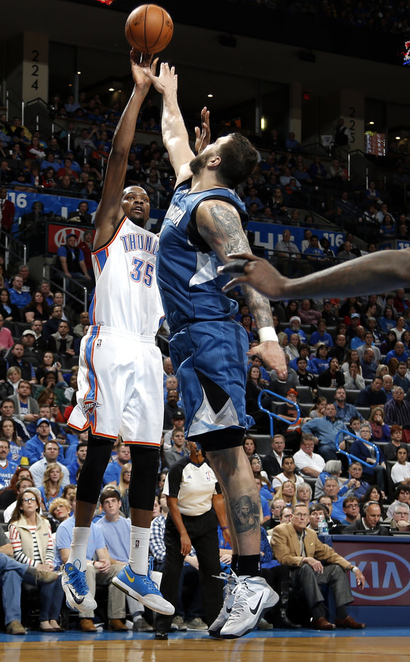 Photo - Oklahoma City's Kevin Durant (35)  shoots over Minnesota's Nikola Pekovic (14)  during the NBA game between the Oklahoma City Thunder and the Minnesota Timberwolves at the Chesapeake Energy Arena, Sunday, Dec. 1, 2013. Photo by Sarah Phipps, The Oklahoman