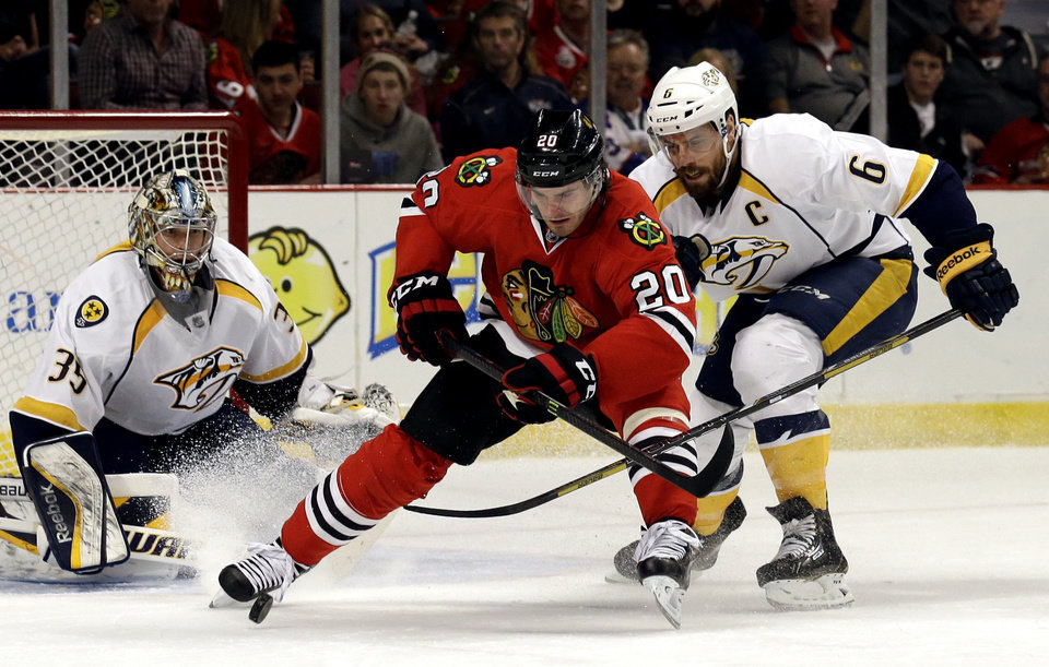 Photo - Chicago Blackhawks' Brandon Saad (20) battles for the puck against Nashville Predators' Shea Weber (6) as goalies Pekka Rinne (35) looks on during the second period of an NHL hockey game in Chicago, Sunday, March 23, 2014. (AP Photo/Nam Y. Huh)