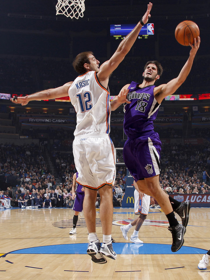 Photo - Oklahoma City's enad Krstic defends Sacramento's Omri Casspi during the NBA basketball game between the Oklahoma City Thunder and the Sacramento Kings at the Ford Center in Oklahoma City, Tuesday, March 2, 2010.  Photo by Bryan Terry, The Oklahoman