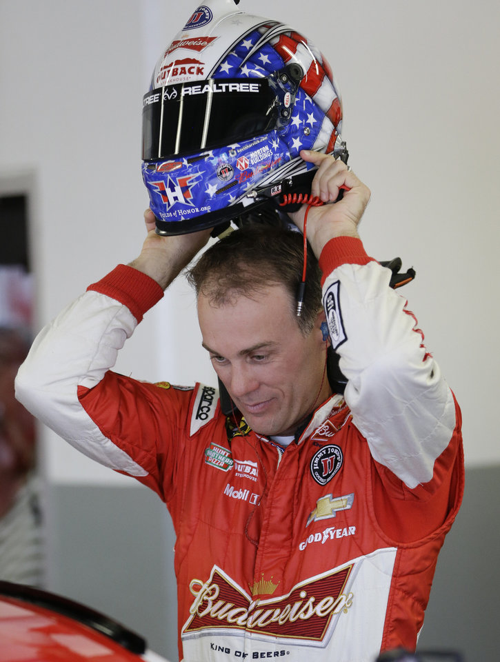Photo - Kevin Harvick puts on his helmet before getting in his car during a NASCAR Sprint Cup practice session at Daytona International Speedway in Daytona Beach, Fla., Thursday, July 3, 2014. (AP Photo/John Raoux)