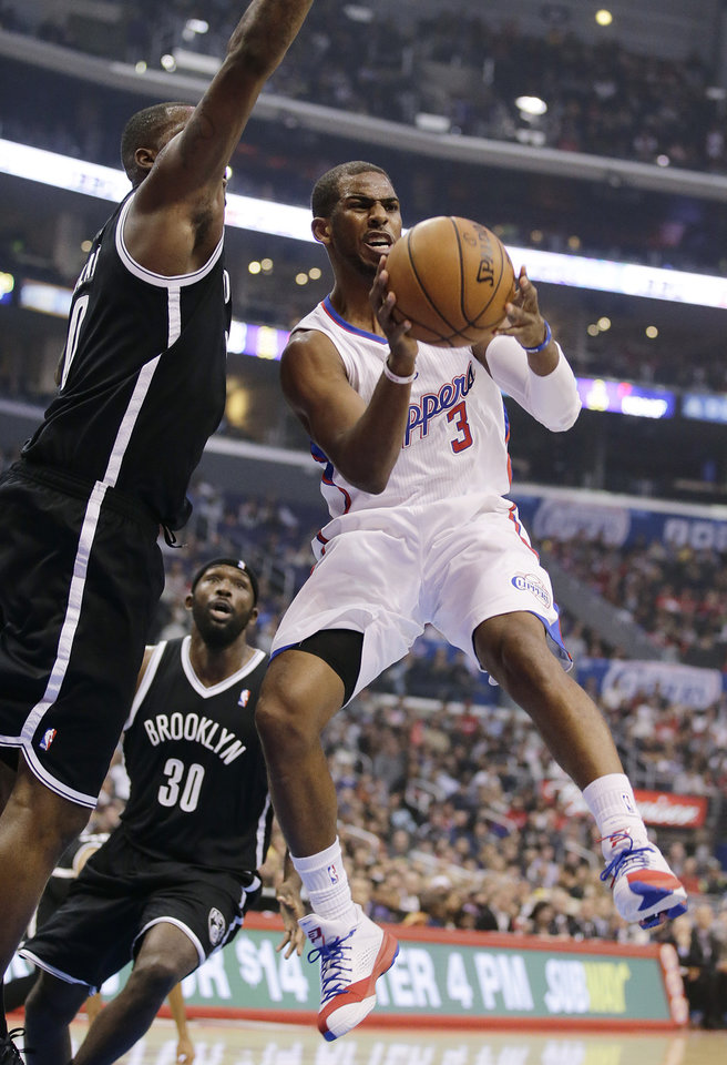 Photo - Los Angeles Clippers' Chris Paul, right, passes the ball as he is defended by Brooklyn Nets' Andray Blatche during the first half of an NBA basketball game on Saturday, Nov. 16, 2013, in Los Angeles. (AP Photo/Jae C. Hong)