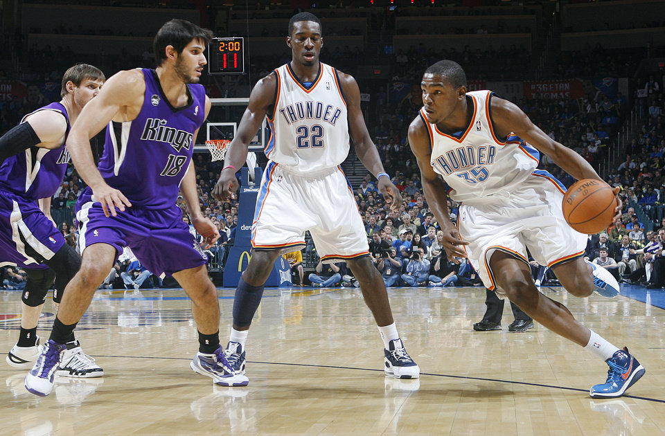 Photo - REGULAR SEASON OPENING NIGHT: Oklahoma City's Kevin Durant (35) drives the ball past the Kings' Omri Casspi (18) during opening night of the Oklahoma City Thunder NBA basketball game against the Sacramento Kings at the Ford Center on Wednesday, Oct. 28, 2009, in Oklahoma City, Okla.  Photo by Chris Landsberger, The Oklahoman ORG XMIT: KOD