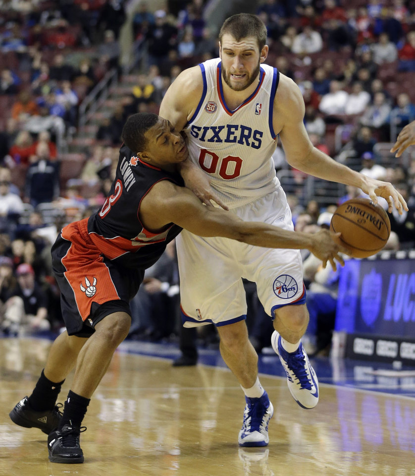Toronto Raptors' Kyle Lowry, left, tries to steal the ball from Philadelphia 76ers' Spencer Hawes in overtime of an NBA basketball game, Friday, Jan. 18, 2013, in Philadelphia. Philadelphia won 108-101. (AP Photo/Matt Slocum)