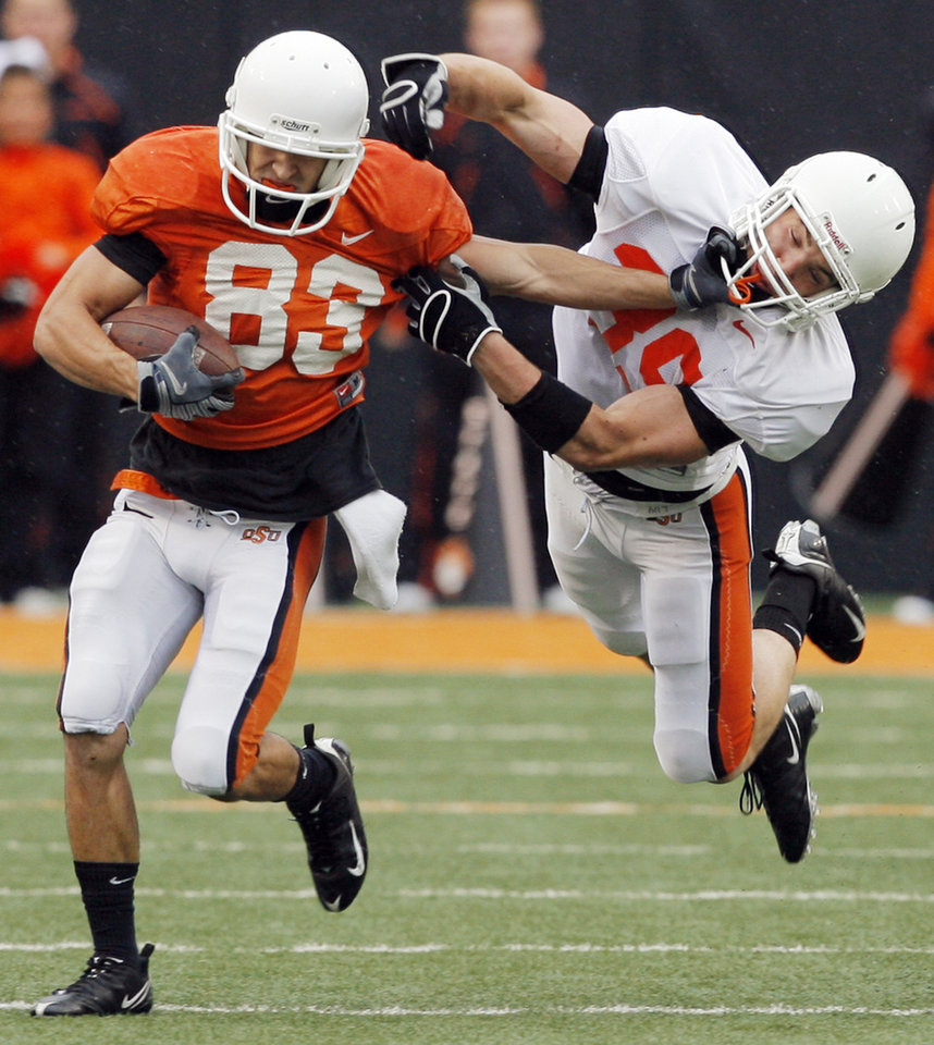 Photo - OSU's Colton Chelf (83) stiff arms Kyle Hale (39) after a reception during the Oklahoma State Orange and White spring football game at Boone Pickens Stadium in Stillwater, Okla., Saturday, April 17, 2010. Photo by Nate Billings, The Oklahoman