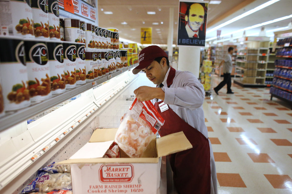 Photo - Market Basket employee Melbi Peraza, of Chelsea, Mass., restocks frozen shrimp at a Market Basket supermarket location, Thursday, Aug. 28, 2014, in Chelsea. A six-week standoff between thousands of employees of the New England supermarket chain and management has ended with the news that the beloved former CEO Arthur T. Demoulas is back in control after buying the entire company. A likeness of Demoulas is attached to a post center top. (AP Photo/Steven Senne)