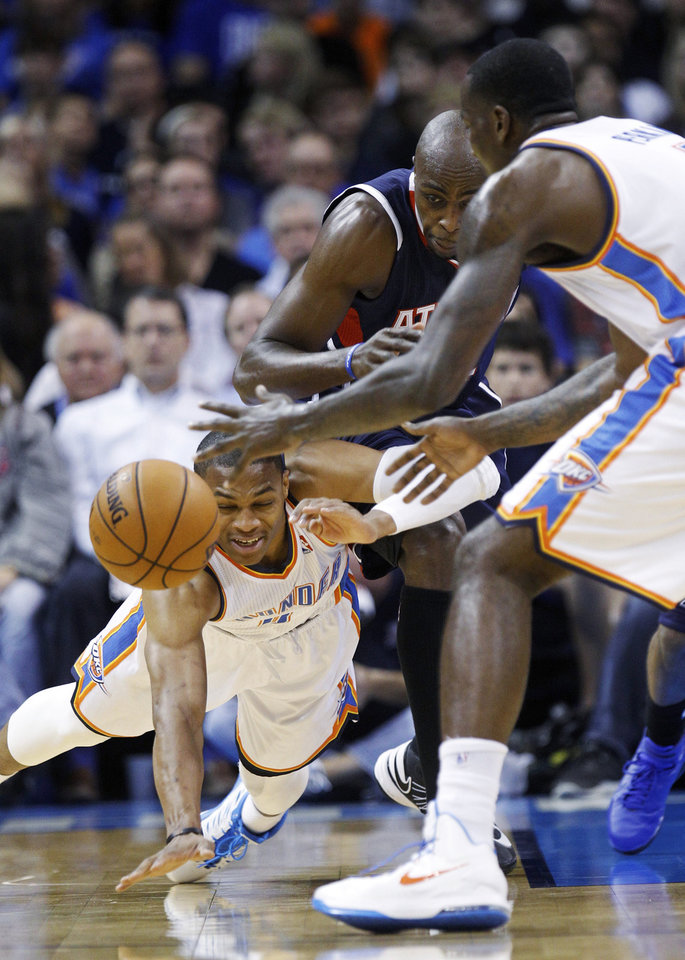 Oklahoma City Thunder guard Russell Westbrook, left, dives for a loose ball in front of Atlanta Hawks forward Anthony Tolliver, center, and Thunder center Kendrick Perkins, right, during the first quarter of an NBA basketball game in Oklahoma City, Sunday, Nov. 4, 2012. (AP Photo/Sue Ogrocki)