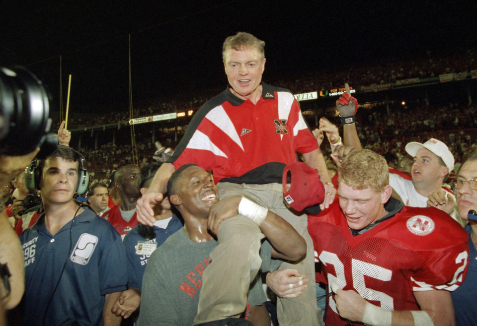 Photo - FILE - In this Jan. 1, 1995 file photo, Nebraska players carry coach Tom Osborne off the field after the Huskers defeated Miami 24-17 in the Orange Bowl NCAA college football game in Miami. Osborne will retire as Nebraska's athletic director on Jan. 1, 2013, and end an association with the university that began in 1962. (AP Photo/Doug Mills, File)