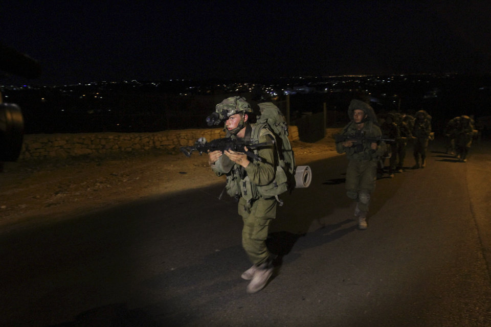 Photo - Israeli soldiers patrol during a military operation to search for three missing teenagers near the West Bank city of Hebron, Sunday, June 15, 2014. A terror group abducted three teens, including an American, who disappeared in the West Bank, Israel's Prime Minister Benjamin Netanyahu said Saturday, as soldiers searched the territory to find them. (AP Photo/Nasser Shiyoukhi)
