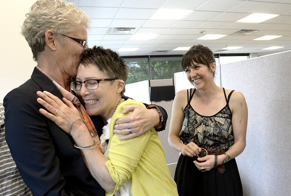 Photo - Julie Hoehing, left, and Nancy Cooley, middle, hug and kiss after they were married, while daughter Lia Cooley watches at the Boulder County Clerk and Recorder's Office in Boulder, Colo., Tuesday, July 1, 2014. Although Colorado's constitution bans same-sex marriage, a ruling from the 10th U.S. Circuit Court of Appeals in Denver last week regarding a Utah case said states cannot prevent people from marrying based on their gender. That motivated Boulder County Clerk Hillary Hall to begin issuing marriage licenses, even though the 10th Circuit put its ruling on hold pending an appeal. (AP Photo/The Daily Camera, Mark Leffingwell)
