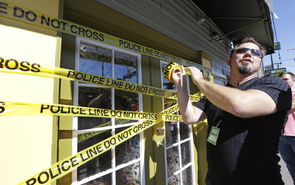 Photo - Cannabis City owner James Lathrop puts up lines of police tape on the front of his shop to cut later for the opening on the first day that sales of recreational pot is legal Tuesday, July 8, 2014, in Seattle. Lathrop is planning on opening for sales at noon. Washington on Tuesday became the second state to allow people to buy marijuana legally in the U.S. without a doctor's note as eager customers who lined up outside stores made their purchases and savored the moment. (AP Photo/Elaine Thompson)