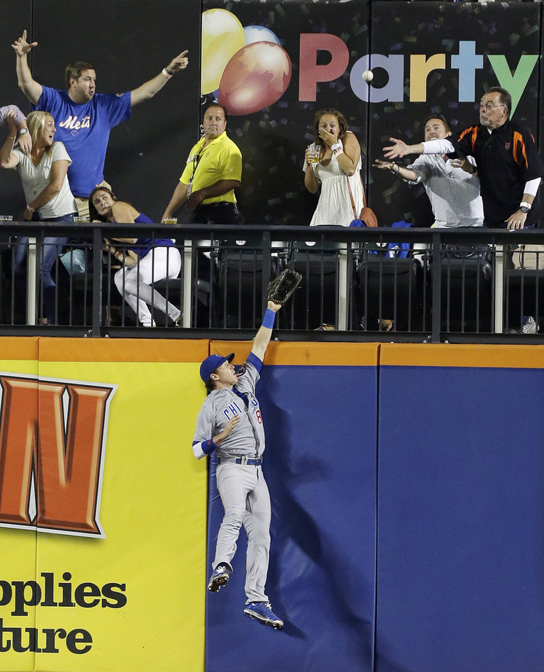 Photo - Chicago Cubs left fielder Chris Coghlan chases a ball hit by New York Mets' Eric Campbell for a three-run home run as fans attempt to make a catch during the fourth inning of a baseball game Friday, Aug. 15, 2014, in New York. (AP Photo/Frank Franklin II)