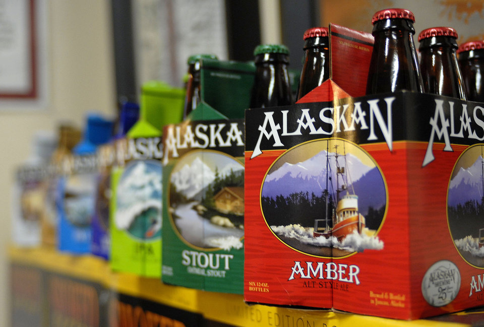 Photo - In this photo taken Jan 23, 2013, in Juneau, Alaska, are six-packs of beer displayed at the Alaskan Brewing Co. The brewery has installed a unique boiler system that burns the company's spent grain the accumulated waste from the brewing process into steam which powers the majority of the plant's operations. (AP Photo/Joshua Berlinger)