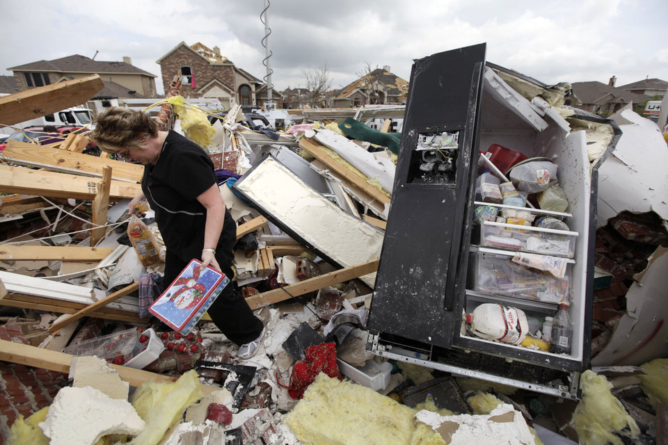 Photo -   Ashley Quinton walks through the tornado damaged home of her friend Sherry Enochs in hopes of finding personal items that can be salvaged Wednesday, April 4, 2012, in Forney, Texas. Enochs was babysitting three children, all under the age of 3, that survived the storm with only minor bumps and scrapes. (AP Photo/Tony Gutierrez)
