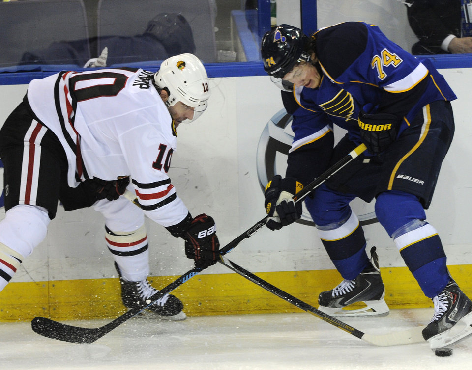 Photo - St. Louis Blues' T.J. Oshie (74) and Chicago Blackhawks' Patrick Sharp (10) reach for the puck during the second period in Game 2 of a first-round NHL hockey playoff series on Saturday, April 19, 2014, in St. Louis. (AP Photo/Bill Boyce)