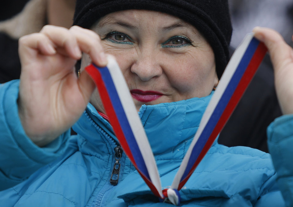 Photo - A pro-Russia demonstrator shows a ribbon in Russian flag colors during a rally in front of the local parliament building in Crimea's capital Simferopol, Ukraine, Thursday, March 6, 2014. About 50 people rallied outside the local parliament Thursday morning waving Russian and Crimean flags. Lawmakers in Crimea called a March 16 referendum on whether to break away from Ukraine and join Russia instead, voting unanimously Thursday to declare their preference for doing so. (AP Photo/Sergei Grits)