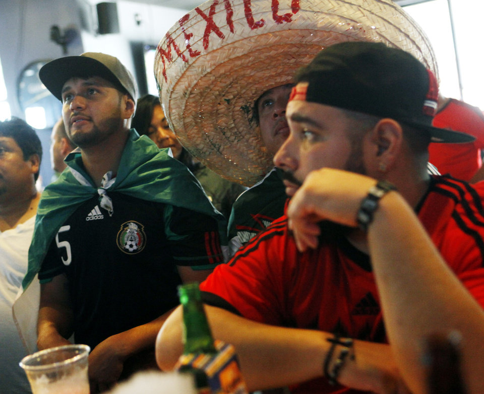 Photo -  Sam Gascon, left, a fan of both the Mexican and American teams, wears a Mexican flag as a cape while he watches the Brazil versus Mexico game Tuesday.    KT King -