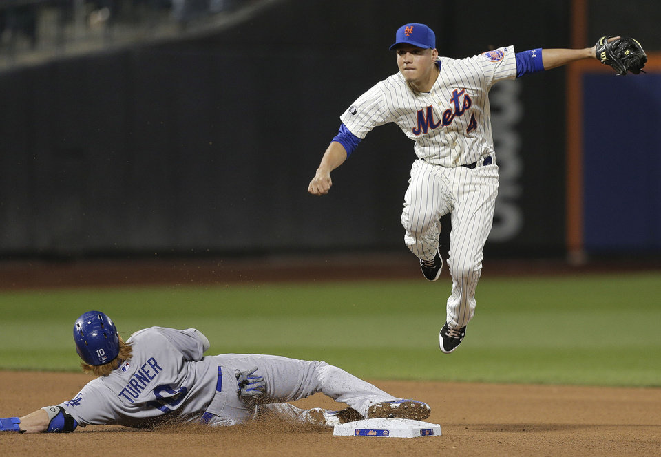 Photo - New York Mets shortstop Wilmer Flores (4) leaps to avoid Los Angeles Dodgers' Justin Turner (10) as he turns a double play during the fifth inning of a baseball game, Thursday, May 22, 2014, in New York. A.J. Ellis was out at first. (AP Photo/Julie Jacobson)