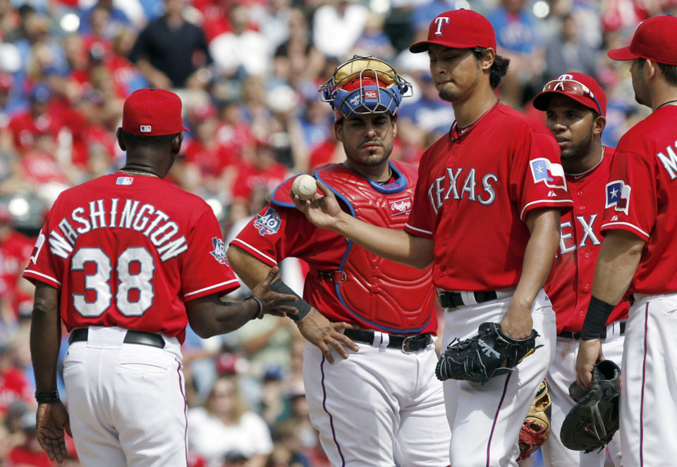 Photo -   Texas Rangers starting pitcher Yu Darvish, third from left, of Japan, is pulled by manager Ron Washington (38) as Geovany Soto, second from left, and Elvis Andrus watch during the seventh inning of the first baseball game of a doubleheader, Sunday, Sept. 30, 2012, in Arlington, Texas. The Angels won 5-4. (AP Photo/LM Otero)