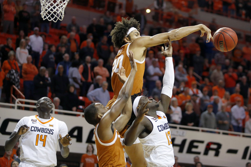 Photo - Texas' Jericho Sims (20) blocks the shot of Oklahoma State's Isaac Likekele (13) during an NCAA basketball game between the Oklahoma State University Cowboys (OSU) and the Texas Longhorns at Gallagher-Iba Arena in Stillwater, Okla., Wednesday, Jan. 15, 2020. [Bryan Terry/The Oklahoman]