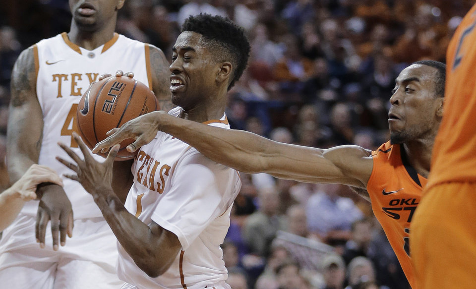Photo - Texas' Isaiah Taylor (1) tries to protect the ball from Oklahoma State's Markel Brown during the first half on an NCAA college basketball game, Tuesday, Feb. 11, 2014, in Austin, Texas. (AP Photo/Eric Gay)