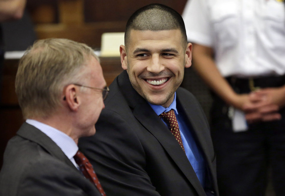 Photo - Former New England Patriots football player AaronHernandez, right, smiles while speaking with his defense attorney Charlie Rankin, left, before a hearing in Suffolk Superior Court, Tuesday, June 24, 2014, in Boston. Prosecutors allege that Hernandez ambushed and shot to death two men, Daniel de Abreu and Safiro Furtado, in 2012 after a chance encounter inside a Boston nightclub. Hernandez has pleaded not guilty. (AP Photo/Steven Senne, Pool)