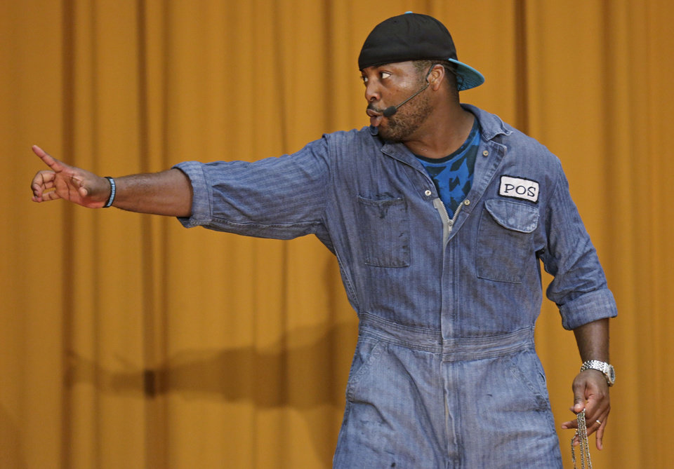 "In this Aug. 27, 2013, photo, rapper Postell Pringle performs in a hip hop adaptation of William Shakespeare's Othello, titled ""Othello: The Remix"" at the Cook County Jail in Chicago. The Q Brothers and Chicago Shakespeare Theater brought the the 70-minute adaptation of William Shakespeare's tragedy to perform for about 450 inmates. This Othello remix is the brainchild of two Chicago brothers and rappers - GQ and JQ, aka Gregory and Jefrrey Qaiyum - who wrote and directed the show, a 40-draft, eight-month project. (AP Photo/M. Spencer Green)"