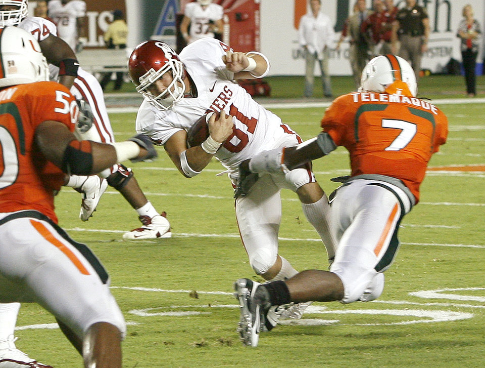 Photo - OU's Carter Whitson drives past Miami's Vaughn Telemaque on a fake field goal during the college football game between the University of Oklahoma (OU) Sooners and the University of Miami (UM) Hurricanes at Land Shark Stadium in Miami Gardens, Florida, Saturday, October 3, 2009. Photo by Bryan Terry, The Oklahoman ORG XMIT: KOD