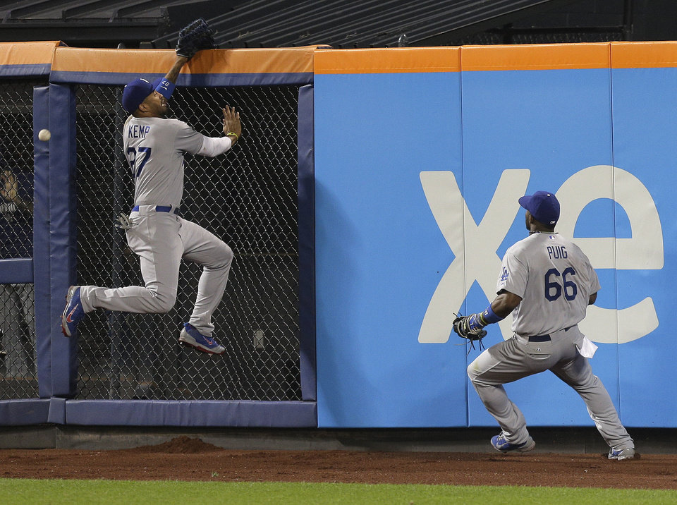 Photo - Los Angeles Dodgers center fielder Matt Kemp (27) leaps unsuccessfully for a ball hit by New York Mets' Curtis Granderson as right fielder Yasiel Puig watches during the eighth inning of a baseball game, Thursday, May 22, 2014, in New York. David Wright scored on the play. (AP Photo/Julie Jacobson)