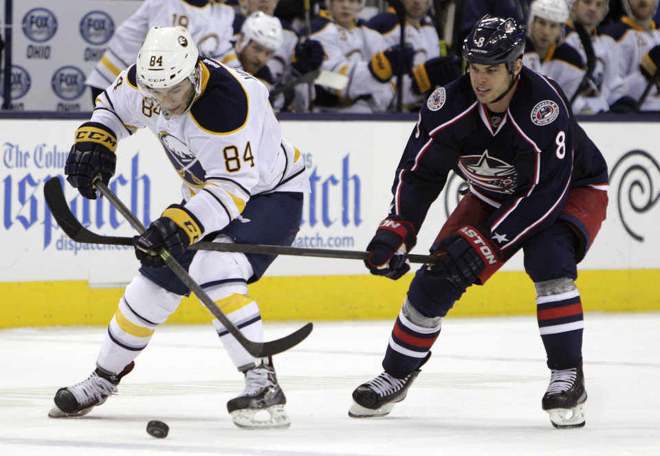 Photo - Buffalo Sabres' Philip Varone, left, carries the puck across the blue line as Columbus Blue Jackets' Nathan Horton defends during the third period of an NHL hockey game, Saturday, Jan. 25, 2014, in Columbus, Ohio. The Sabres won 5-2. (AP Photo/Jay LaPrete)