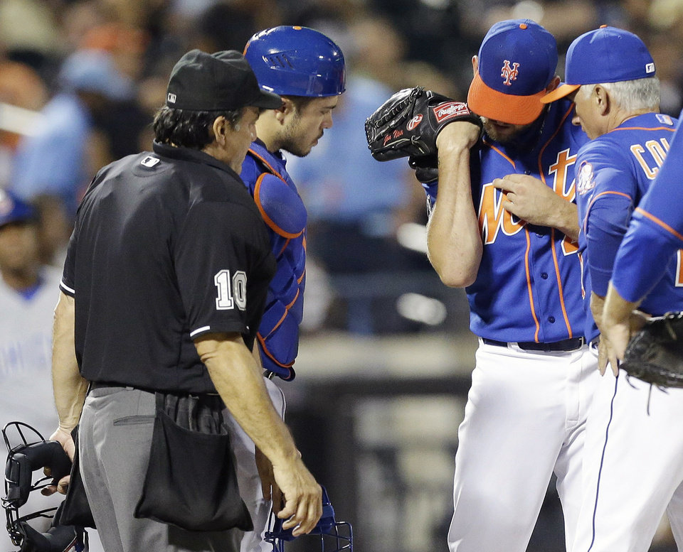 Photo - New York Mets manager Terry Collins, right, and home plate umpire Phil Cuzzi (10) look at the arm of starting pitcher Jonathon Niese after he was hurt on a play during the seventh inning of a baseball game against the Chicago Cubs, Saturday, Aug. 16, 2014, in New York. (AP Photo/Frank Franklin II)