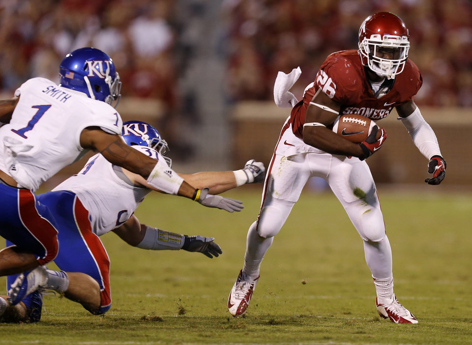 OU\'s Damien Williams (26) runs past KU\'s Lubbock Smith (1) and Ben Heeney (31) during the college football game between the University of Oklahoma Sooners (OU) and the Kansas Jayhawks (KU) at Gaylord Family-Oklahoma Memorial Stadium in Norman, Okla., Saturday, Oct. 20, 2012. Photo by Bryan Terry, The Oklahoman