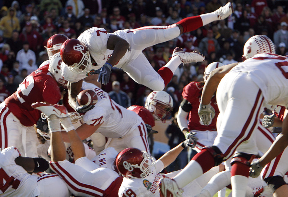 Photo - Oklahoma's DeMarco Murray (7) goes over the top to score the game winning touchdown during the second half of the Brut Sun Bowl college football game between the University of Oklahoma Sooners (OU) and the Stanford University Cardinal on Thursday, Dec. 31, 2009, in El Paso, Tex. Oklahoma won 31-27.   Photo by Chris Landsberger, The Oklahoman