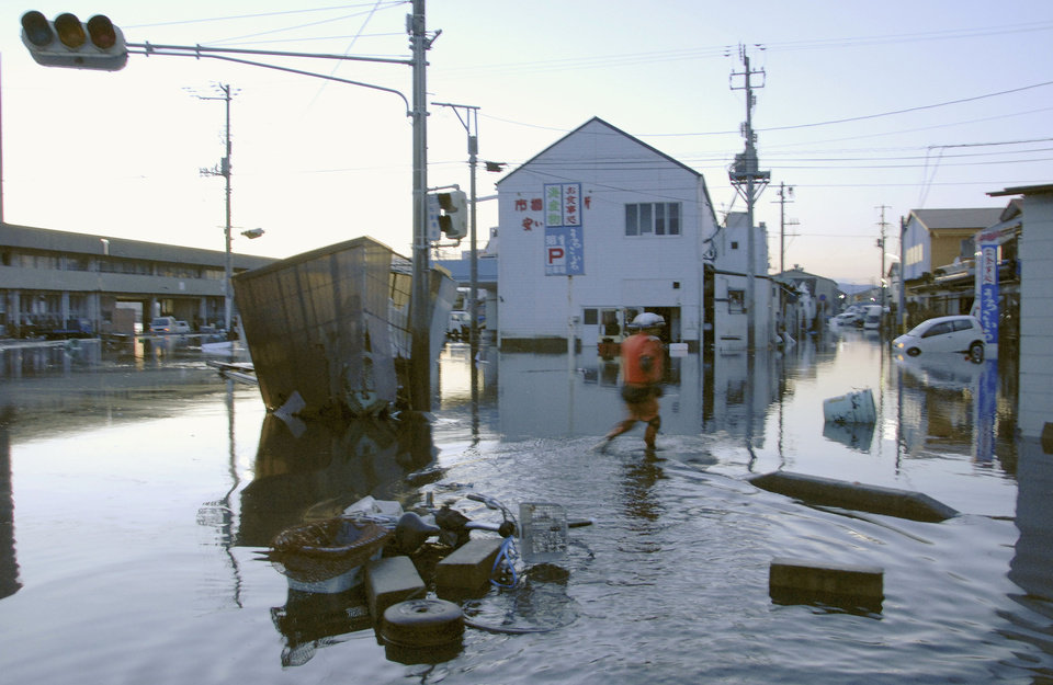 Photo - A man wades through a flooded street after tsunami spawned by a powerful earthquake in Iwaki, Fukushima prefecture (state), Japan, Friday, March 11, 2011.  The largest earthquake in Japan's recorded history slammed the eastern coast Friday. (AP Photo/Kyodo News) JAPAN OUT, MANDATORY CREDIT, FOR COMMERCIAL USE ONLY IN NORTH AMERICA ORG XMIT: TTX801