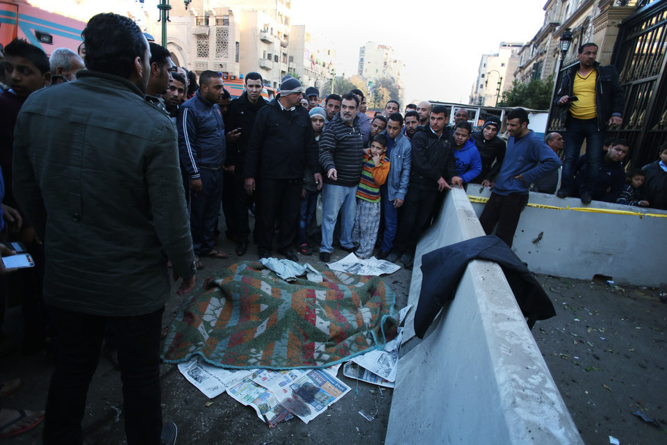 Photo - People surround a body covered with a blanket on the street after a car bomb explosion at the Egyptian police headquarters in downtown Cairo, Friday, Jan. 24, 2014. A car bomb struck the main Egyptian police headquarters Friday in the heart of Cairo, killing at least several people in a hugely symbolic attack on the eve of the third anniversary of the 2011 uprising that toppled longtime autocratic ruler Hosni Mubarak. (AP Photo/Khalil Hamra)