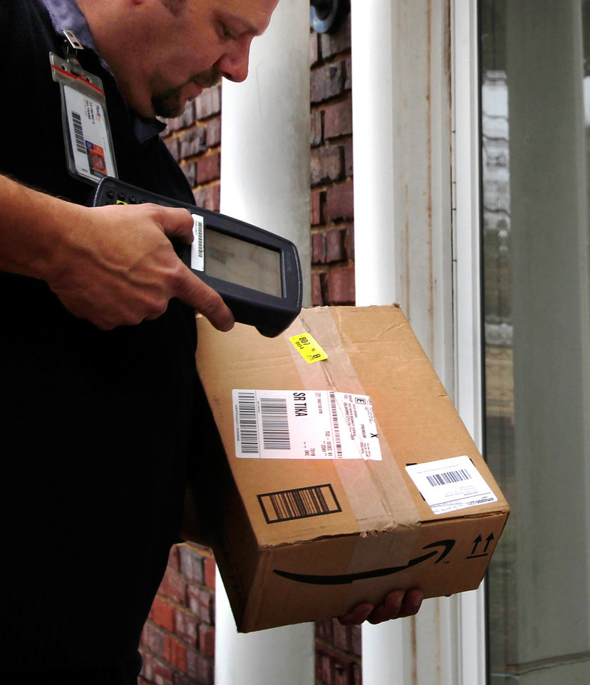 Longtime FedEx driver Ray Beltrane uses a scanning device on the label of this package before he delivers it to a home in northwest Oklahoma City on Monday, Dec. 12, 2011. Photo by Jim Beckel, The Oklahoman