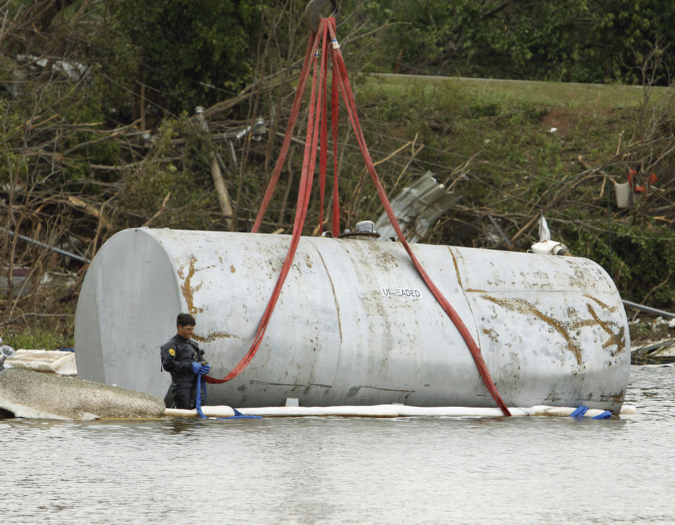 A salvage diver attaches a harness to a gasoline tank that was blown from it's concrete enclosure into Lake Thunderbird on Wednesday, May 12, 2010, in Norman, Okla.   The tank at the Marina on East Alameda landed upright and did not spill its contents into the lake.  Photo by Steve Sisney, The Oklahoman