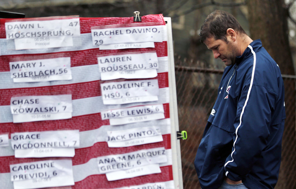 Photo - A man pays respects near a U.S. flag donning the names of victims on a makeshift memorial in the Sandy Hook village of Newtown, Conn., as the town mourns victims killed in a school shooting, Monday, Dec. 17, 2012. Authorities say a gunman killed his mother at their home and then opened fire inside the Sandy Hook Elementary School in Newtown, killing 26 people, including 20 children, before taking his own life, on Friday. (AP Photo/Julio Cortez)