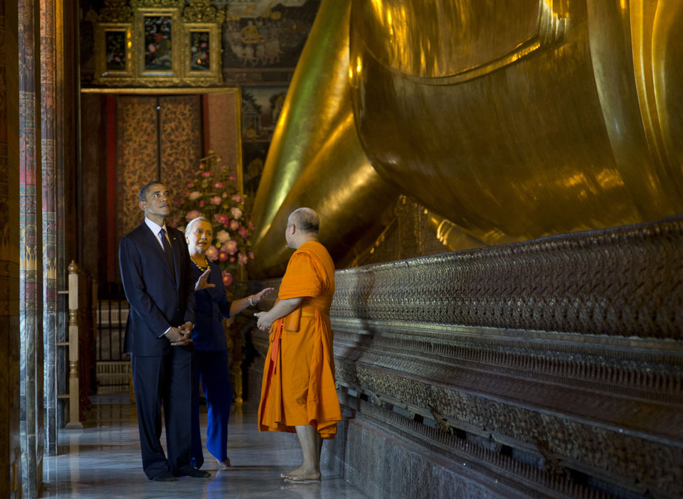 Photo -   U.S. President Barack Obama, left, and U.S. Secretary of State Hillary Rodham Clinton, center, tour the Viharn of the Reclining Buddha with Chaokun Suthee Thammanuwat, the Dean, Faculty of Buddhism Assistant to the Abbot of Wat Phra Chetuphon at the Wat Pho Royal Monastery in Bangkok, Thailand, Sunday, Nov. 18, 2012. (AP Photo/Carolyn Kaster)