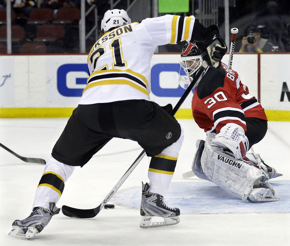 Photo - Boston Bruins' Loui Eriksson, of Sweden, (21) shoots for a goal past New Jersey Devils goalie Martin Brodeur (30) during the first period of an NHL hockey game in Newark, N.J., Sunday, April 13, 2014. (AP Photo/Mel Evans)