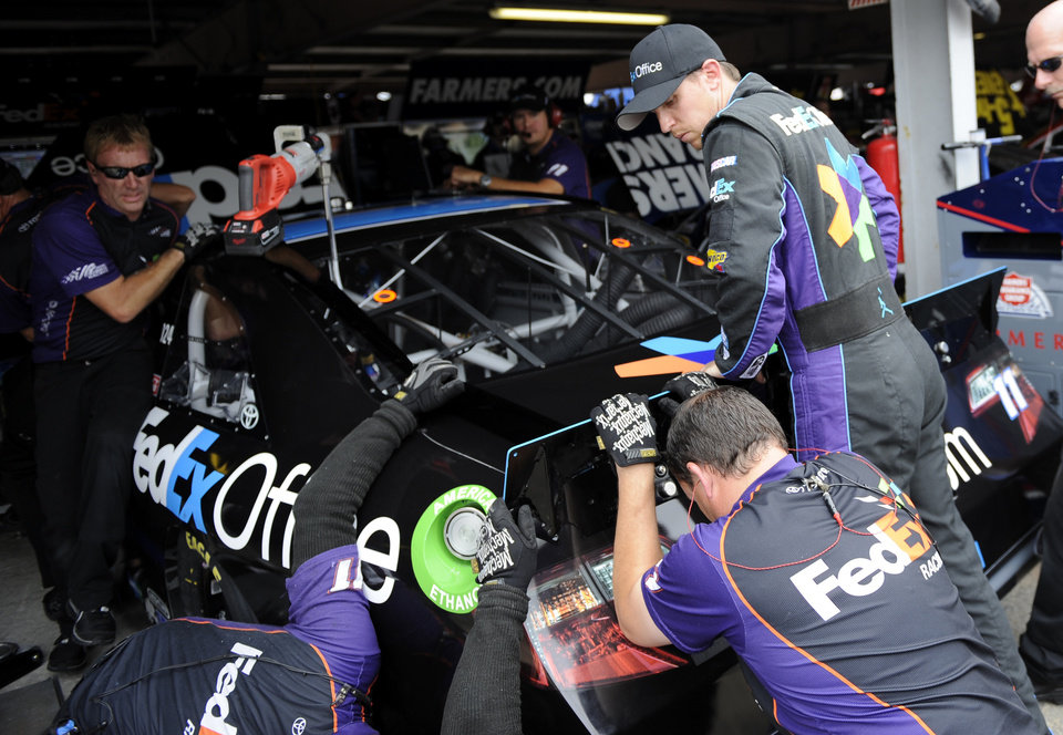 Sprint Cup Series driver Denny Hamlin, right, watches his pit crew work on his race car during practice for the AAA 400 NASCAR Sprint Cup Series auto race, Friday, Sept. 28, 2012, in Dover, Del. (AP Photo/Nick Wass)