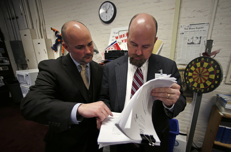 Jonathan Scalise, owner of Ammunition Storage Components of New Britian, Conn., left, examines a draft of gun control legislation before it is presented on the House floor with shooting sports lobbyist John Larkin, right, in the press room at the Capitol in Hartford, Conn., Wednesday, April 3, 2013. Hundreds of gun rights advocates are gathering at the statehouse in Hartford ahead of a vote in the General Assembly on proposed gun-control legislation. Scalise is concerned with the impact of the bill on his business and employees. (AP Photo/Charles Krupa)
